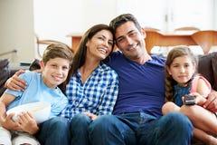 Familjsammanträde på Sofa Watching TV tillsammans Royaltyfri Fotografi