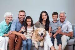 Familjsammanträde på soffan med hunden royaltyfria bilder