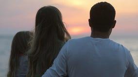 Familjsammanträde på stranden på solnedgångsikten från lager videofilmer