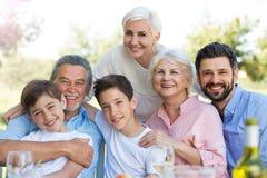 Familjsammanträde på tabellen utomhus och att le Royaltyfria Foton