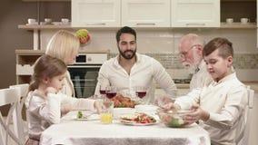Familjsammanträde runt om en tabell och att äta, meddela och havande gyckel under familjmatställe stock video