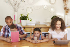 Familjsammanträde runt om hemmastadd användande teknologi för tabell arkivbild
