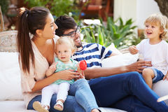 Familjsammanträde utomhus i trädgårds- hemmastatt tillsammans royaltyfri bild