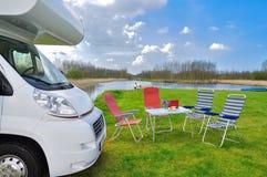 Familjsemester, begrepp för RV-camparelopp, motorhome, tabell och stolar i campingplats, ungar på bakgrund Arkivfoto