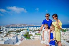 Familjsemester i Europa Föräldrar och ungar som tar den Mykonos för selfiefotobakgrund staden i Grekland Arkivbild