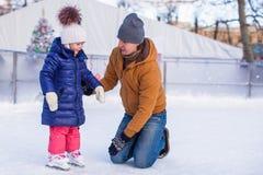 Familjsemester på att åka skridskor isbanan Royaltyfria Foton