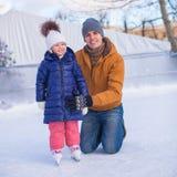 Familjsemester på att åka skridskor isbanan Arkivbild