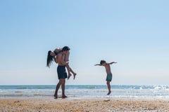 Familjsemester på kustmodern i händerna av påven och bredvid sonen på stranden Fotografering för Bildbyråer