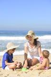 Familjsemester på stranden: Moder och ungar Arkivbild