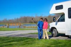 Familjsemester, RV-lopp, lycklig pardanandeselfie nära camparen på ferietur i motorhome Arkivbild