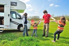 Familjsemestern, RV-camparelopp med ungar, föräldrar med barn på ferie snubblar i motorhome Arkivfoto