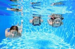 Familjsimning i pöl under vatten, den lyckliga aktiva modern och barn har gyckel, kondition och sporten med ungar