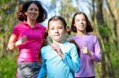 Familjsport, lycklig aktiv moder och ungar som utomhus joggar Arkivfoto