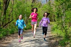 Familjsport, lycklig aktiv moder och ungar som utomhus joggar Arkivfoton