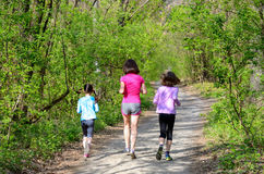 Familjsport, lycklig aktiv moder och ungar som utomhus joggar Arkivbild