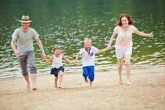 Familjspring på stranden på sommar royaltyfri foto