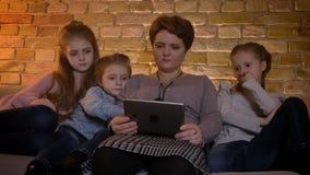 Familjstående av den caucasian modern och döttrar som uppmärksamt håller ögonen på in i minnestavlan i mysig hem- atmosfär stock video