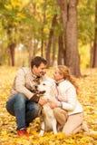 Familjstående av den unga mannen och kvinnan med hans hundlabrador I Arkivfoto