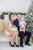 Familjstående för lycklig jul Att le uppfostrar med behandla som ett barn dottern hemma som firar nytt år jul min version för por Royaltyfri Bild
