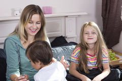 Familjstående i säng hemma Arkivbild