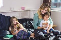 Familjstående i säng hemma arkivfoton