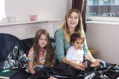 Familjstående i säng hemma royaltyfri fotografi