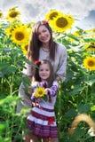 Familjstående i solrosor Royaltyfria Bilder