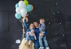 Familjstående med ballonger i studion Royaltyfri Foto