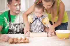 Familjstående, medan laga mat Royaltyfria Bilder