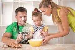 Familjstående, medan laga mat Arkivfoto