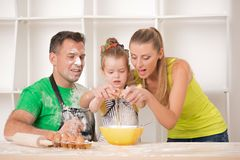 Familjstående, medan laga mat Royaltyfri Fotografi