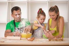 Familjstående, medan laga mat Royaltyfri Bild
