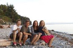 Familjstående på en stenig kust- strand Royaltyfria Bilder