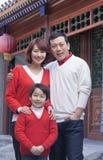 Familjstående utanför vid en byggnad för traditionell kines royaltyfria foton