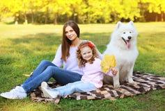 Familjståenden, nätt barn fostrar, och barnet går med hunden arkivfoto