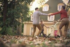 Familjtid, föräldrar som utanför spelar med barn royaltyfri bild