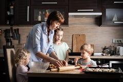 Familjtid: Mamma med tre barn som förbereder kakor i köket Verklig autentisk familj royaltyfri bild