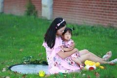 Familjtid, moder kramar hennes litet behandla som ett barn flickan på gräsmattan Fotografering för Bildbyråer