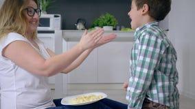 Familjunderhållning, mum med barnet spelas för matsammanträde på golv inomhus arkivfilmer