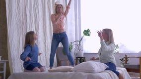 Familjunderhållning, roliga flickadöttrar sjunger och bedragit för lycklig Mum, medan ha gyckel på säng hemma stock video