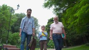 Familjutvecklingsbegrepp: Fader, son och farfar, utomhus, i naturen som tillsammans tycker om deras kvalitets- Tid, allt in lager videofilmer