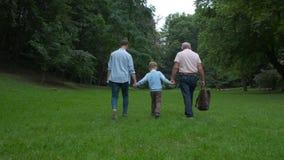 Familjutvecklingsbegrepp: Fader, son och farfar, utomhus, i naturen som tillsammans tycker om deras kvalitets- Tid, allt in arkivfilmer