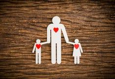 Famille à chaînes de papier et coeur rouge symbolisant Photos libres de droits
