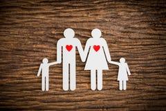 Famille à chaînes de papier et coeur rouge symbolisant Photographie stock libre de droits