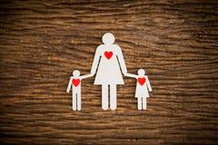 Famille à chaînes de papier et coeur rouge symbolisant Images libres de droits