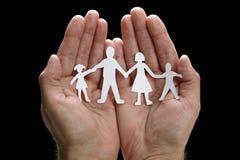 Famille à chaînes de papier protégée dans des mains évasées Image stock