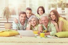 Famille à la maison avec l'ordinateur portatif Image stock