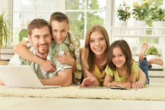 Famille à la maison avec l'ordinateur portatif Photo stock
