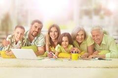 Famille à la maison avec l'ordinateur portatif Images libres de droits