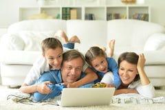 Famille à la maison avec l'ordinateur portatif Photographie stock